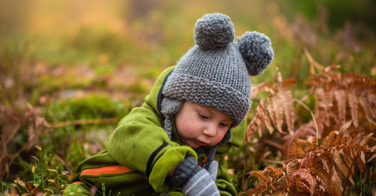 A little boy that is standing in the grass